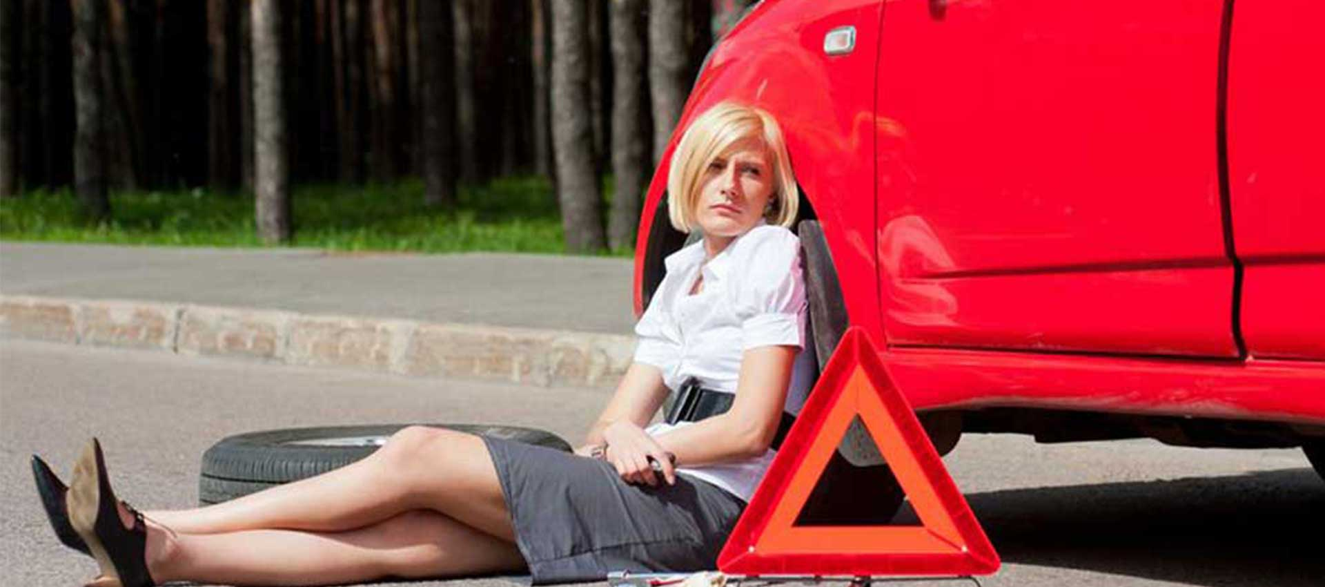 Woman sitting next to a red car.